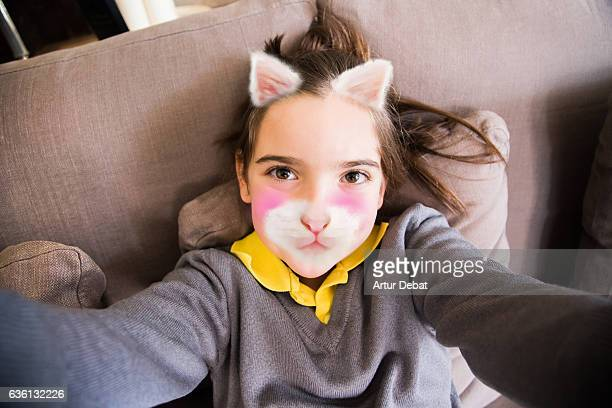 little girl using smartphone application changing her face with kitten face. - toned image stock pictures, royalty-free photos & images
