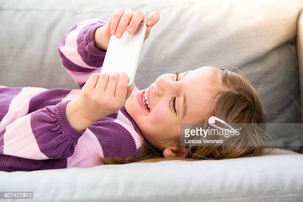 little girl using smartphone on sofa - larissa veronesi stock pictures, royalty-free photos & images