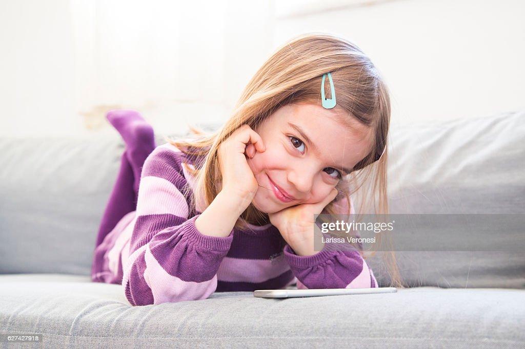 little girl using smartphone on sofa : Stock Photo