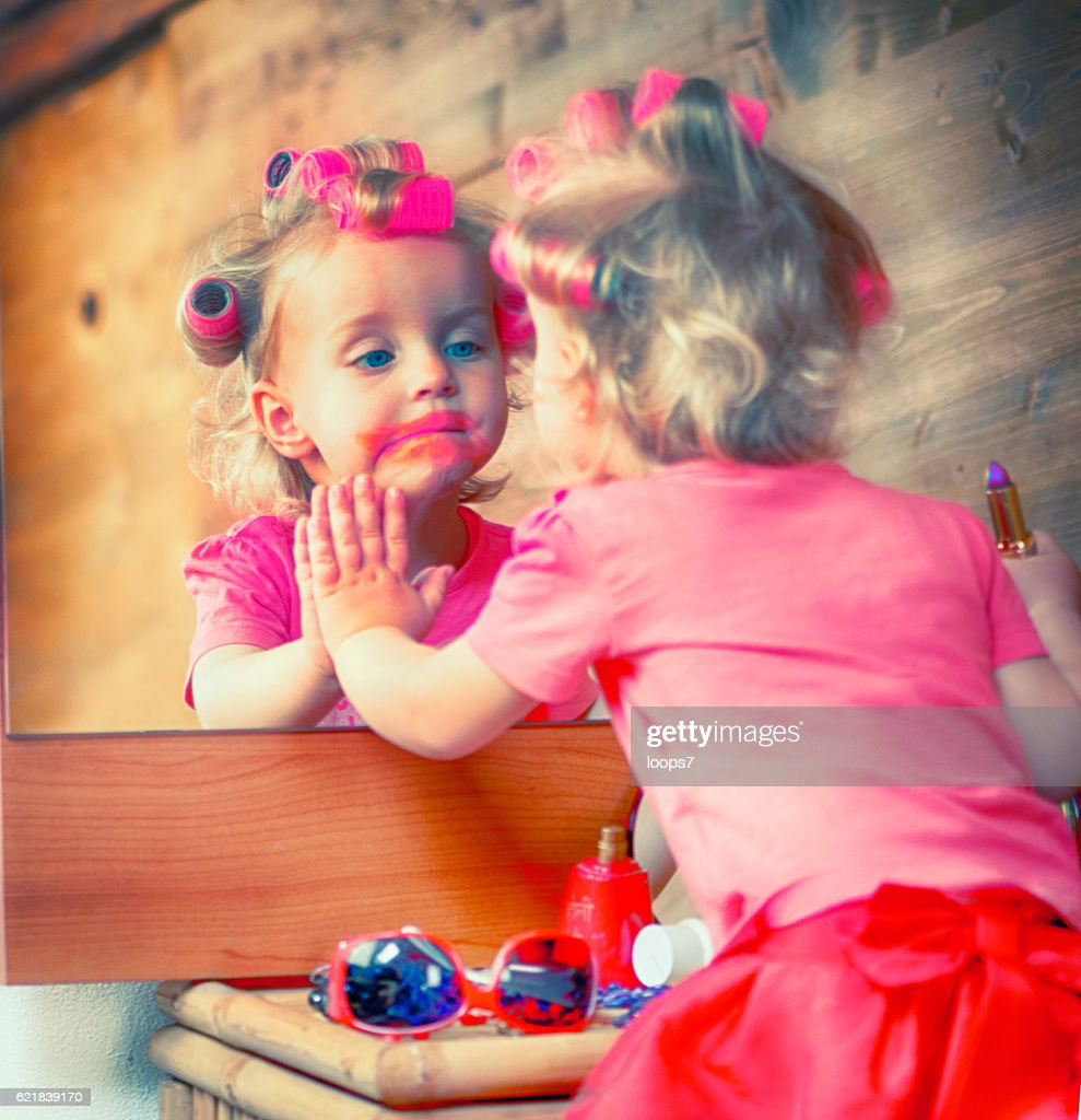 Little girl using the red lipstick : Stock Photo