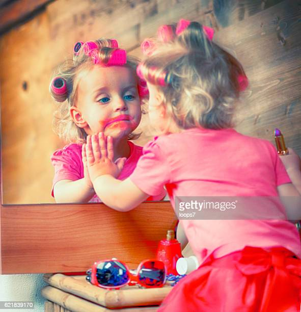 little girl using the red lipstick - girl in mirror stock photos and pictures