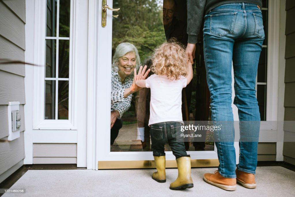 Little Girl Visits Grandparents Through Window : Stock Photo