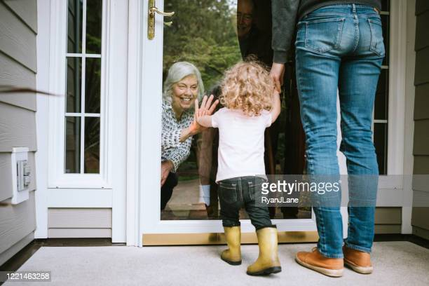 little girl visits grandparents through window - social distancing stock pictures, royalty-free photos & images