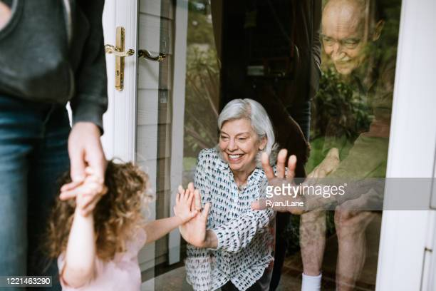 little girl visits grandparents through window - quarantine stock pictures, royalty-free photos & images