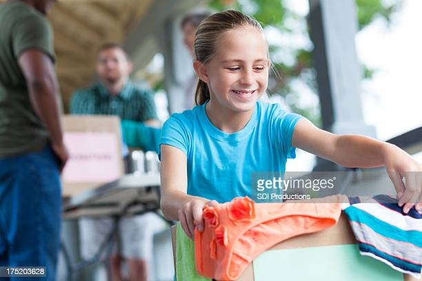 little girl volunteering at charity clothing donation event - garage sale stock pictures, royalty-free photos & images