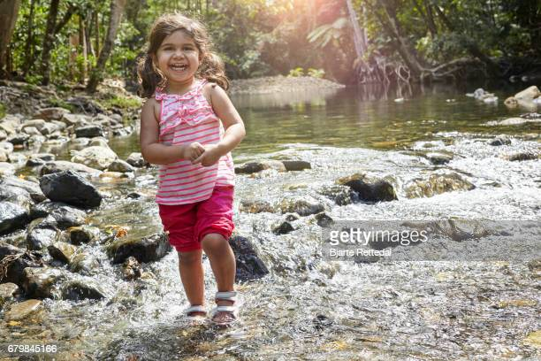 Little girl wading in water stream in The Daintree National Park, Queensland, Australia