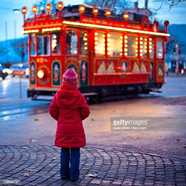 Little girl waiting for Santa's red tram