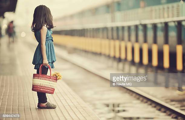 Little girl waiting in a railway station.