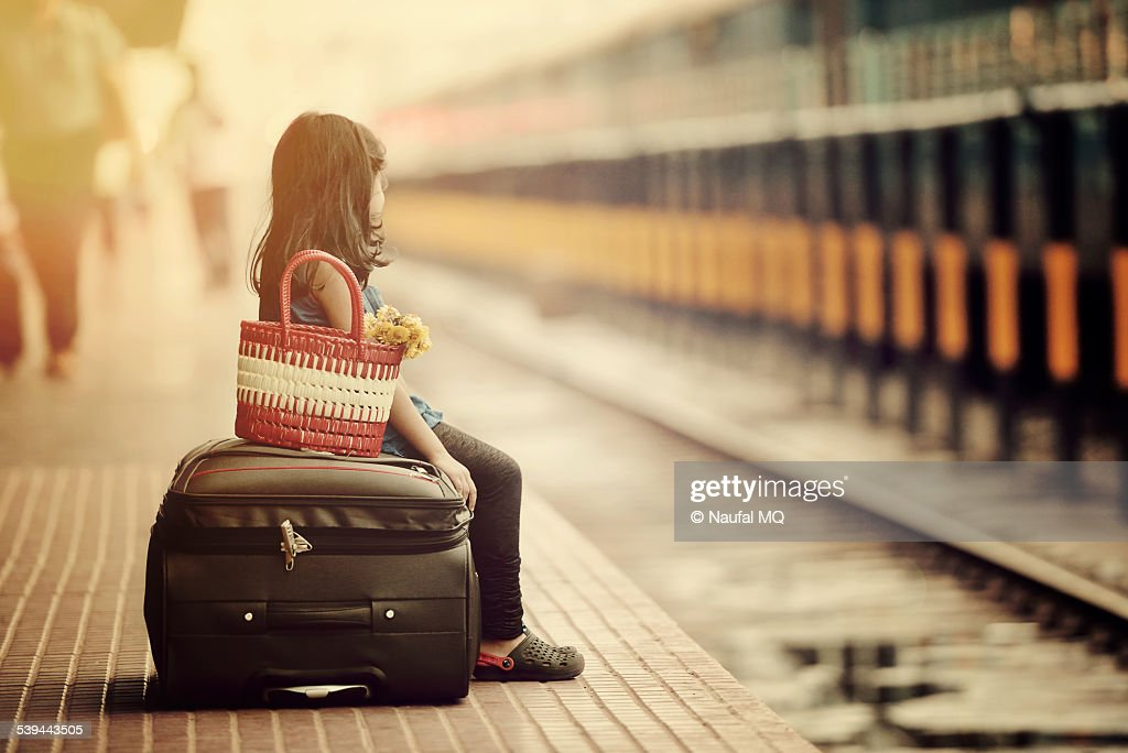 Little girl waiting in a railway station : Stock Photo