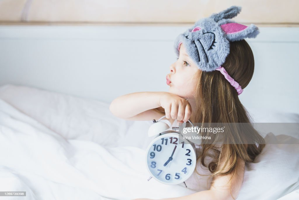 Little girl wakes up in morning under white blanket wearing grey bunny plush sleep mask with alarm clock in her hands. Child sleep regime hours. Early rise to kindergarten. Mom's daily rest routine : Stock Photo