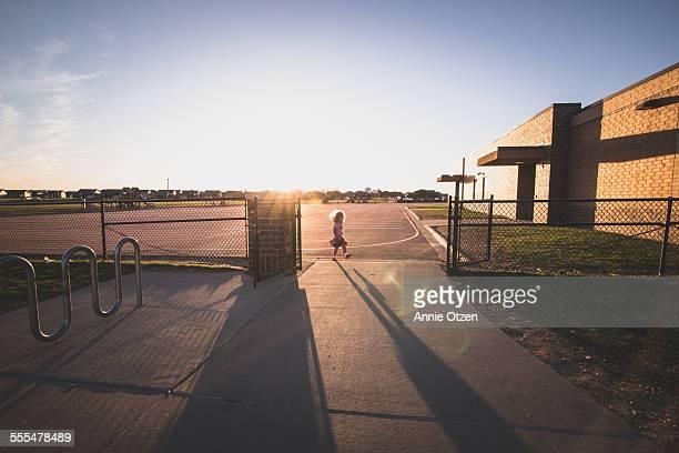 Little girl waling through gate