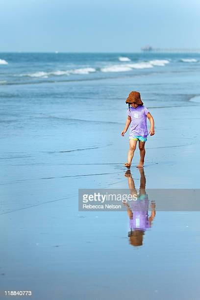 little girl walking along ocean shore - rebecca nelson stock pictures, royalty-free photos & images