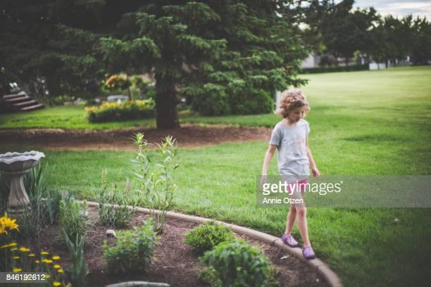 Little Girl Walking around a Garden