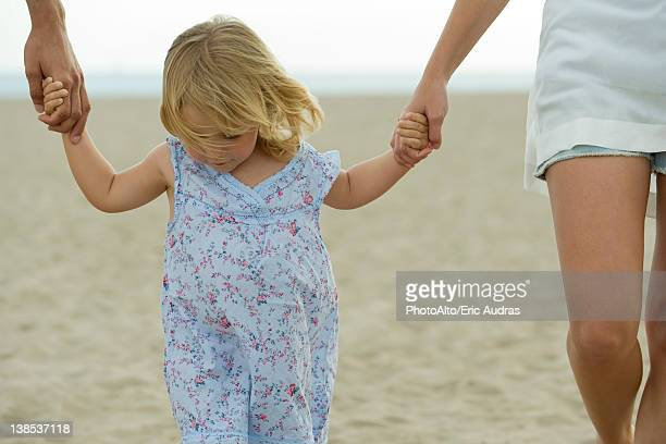 Little girl walking hand in hand with parents at the beach, cropped