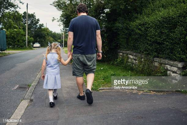 little girl walking holding her fathers hand - one parent stock pictures, royalty-free photos & images