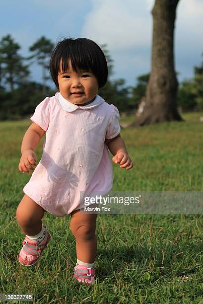 little girl walking in grass - yonago stock photos and pictures