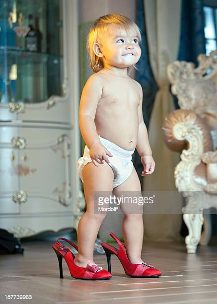 little girl walking in red high heels shoes - diaper kids stock pictures, royalty-free photos & images