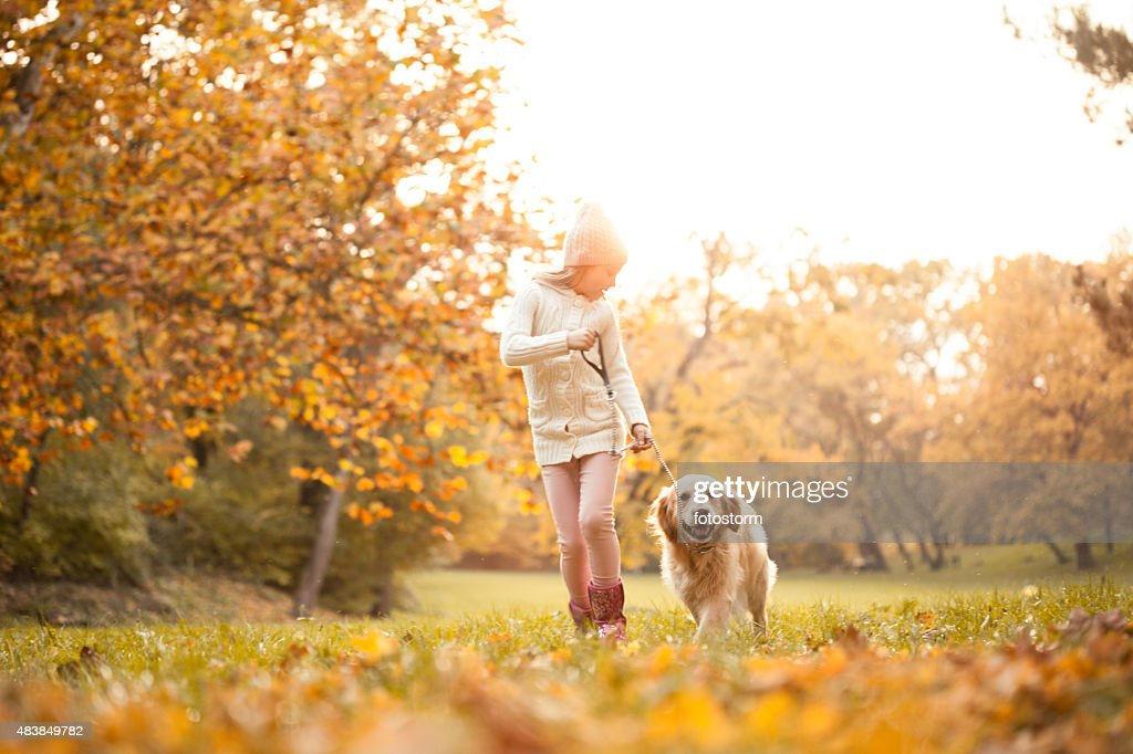 Little girl walking in the park with her dog : Stock Photo
