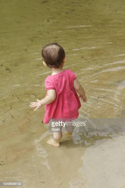 Little girl walking in the water