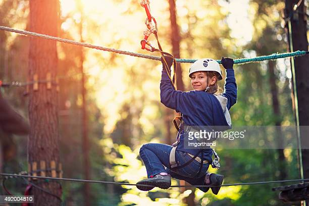 Little girl walking on line in ropes course adventure park