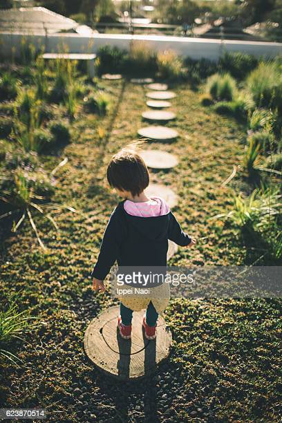 Little girl walking on stepping stones on green rooftop