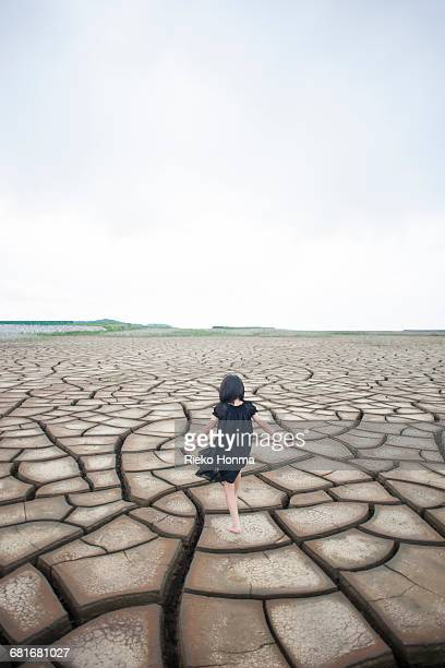 Little girl walking on the dry land