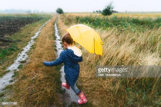 Little girl walking on the field under the rain