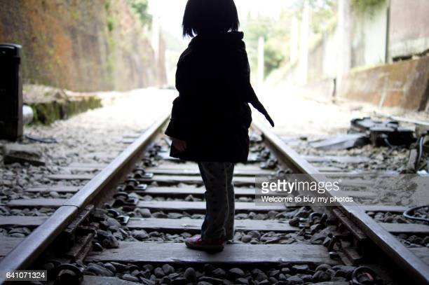 little girl walking on the railroad track of shengxing railway station, miaoli taiwan. - child abuse stock pictures, royalty-free photos & images