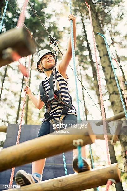 Little girl walking on the ropes course
