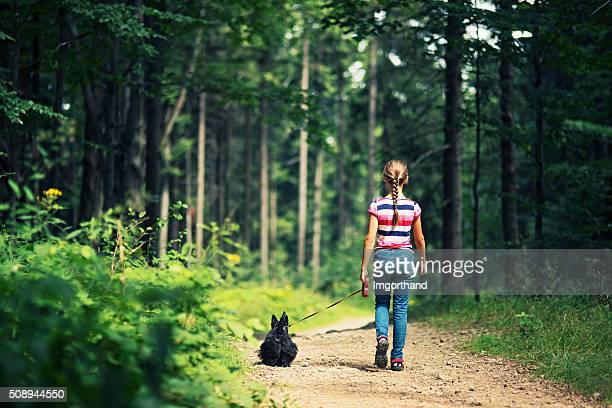 Little girl walking with dog in a forest