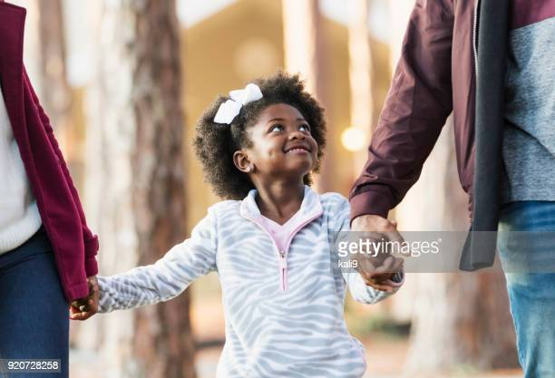 little girl walking with family, looking at father - mid section stock photos and pictures