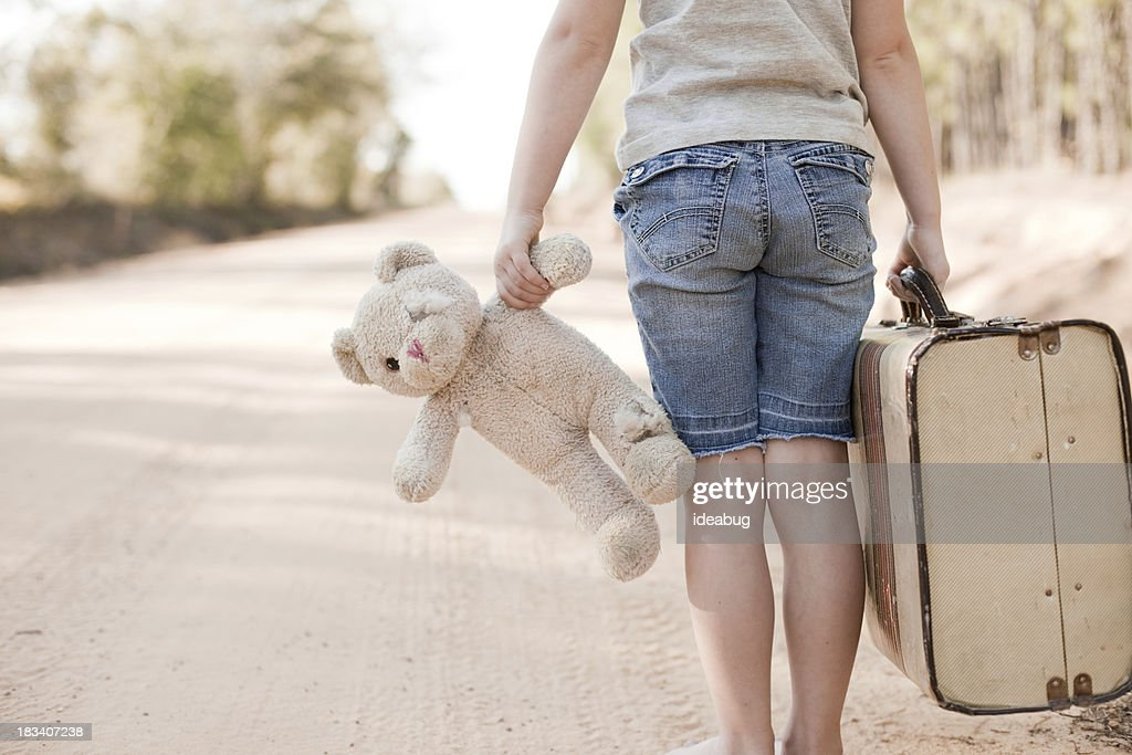 Little Girl Walking with Old Teddy Bear and Suitcase : Stock Photo