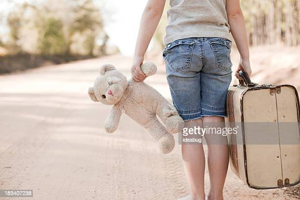 little girl walking with old teddy bear and suitcase - bear tracks stock photos and pictures