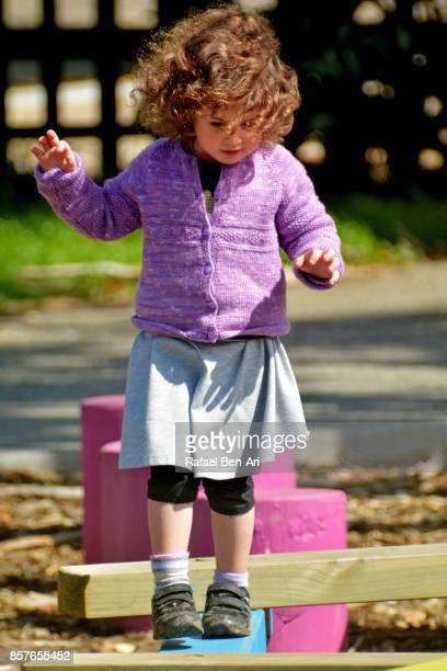 little girl walks on balance beams - rafael ben ari fotografías e imágenes de stock