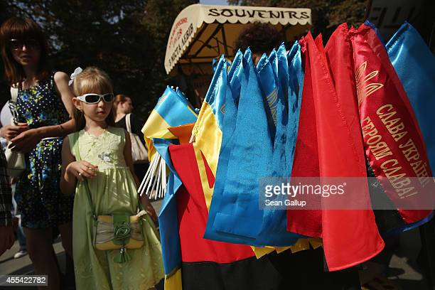 A little girl walks past a vendor's stall selling Ukrainian flags and the red and black flags of the 1940s Ukrainian Insurgent Army decorated with...