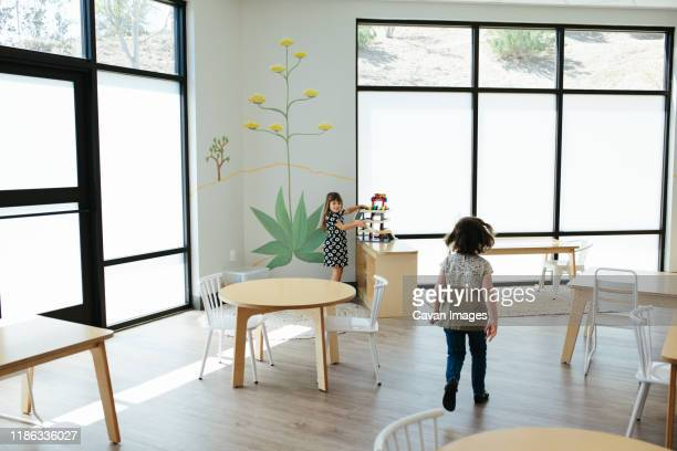 little girl walks toward smiling girl who is holding a toy - calabasas stock pictures, royalty-free photos & images