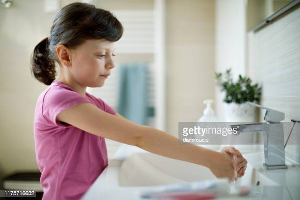 little girl washing hands in the bathroom - damircudic stock photos and pictures