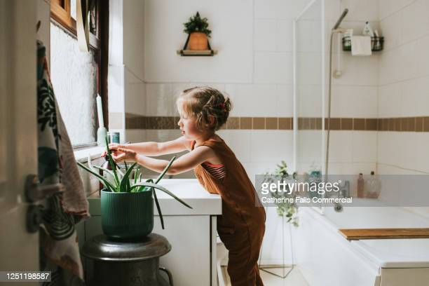 little girl washing her hands at a bathroom sink - reaching stock pictures, royalty-free photos & images