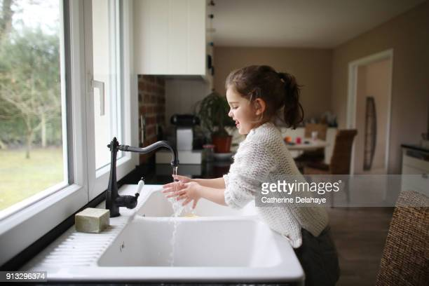 a little girl washing her hands in the kitchen - lavar manos fotografías e imágenes de stock