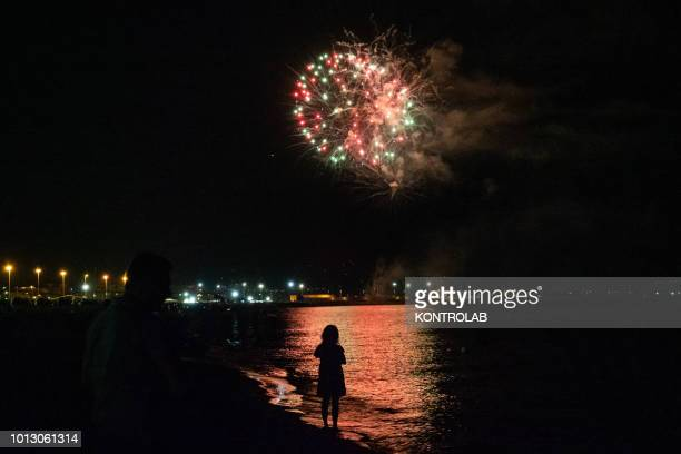 SCHIAVONEA CORIGLIANO CALABRIA ITALY A little girl watch the fireworks by the sea during the summer party for Santa Maria Ad Nives held in Corigliano...