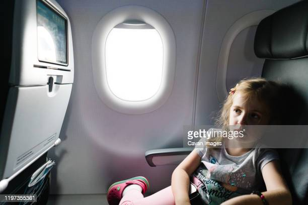 a little girl watches a movie on an airplane. - toddler at airport stock pictures, royalty-free photos & images