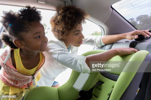 Little girl watches mother install car seat