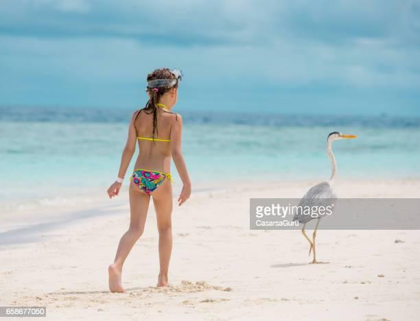 Meisje kijken reiger op het strand van de Maldiven