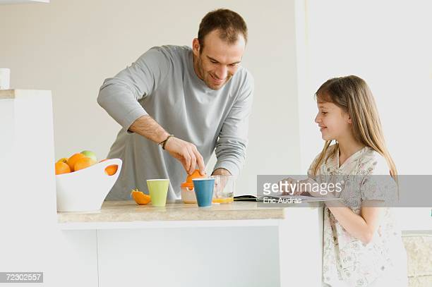 Little girl watching man squeezing oranges in the kitchen