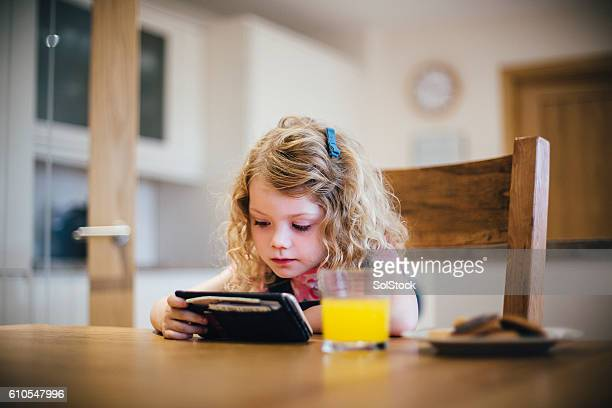 little girl watching tv on a smartphone - television show stock pictures, royalty-free photos & images