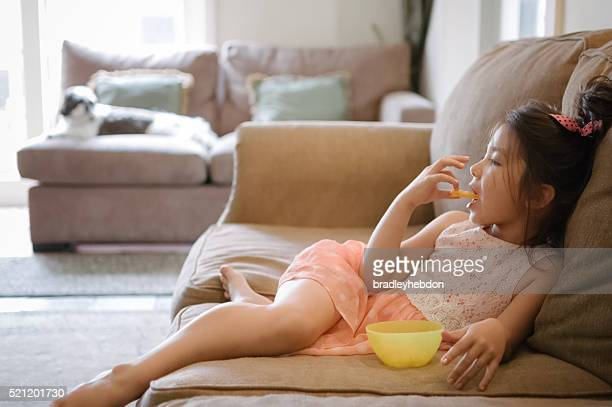little girl watching tv while eating snack at home - girls open mouth stockfoto's en -beelden