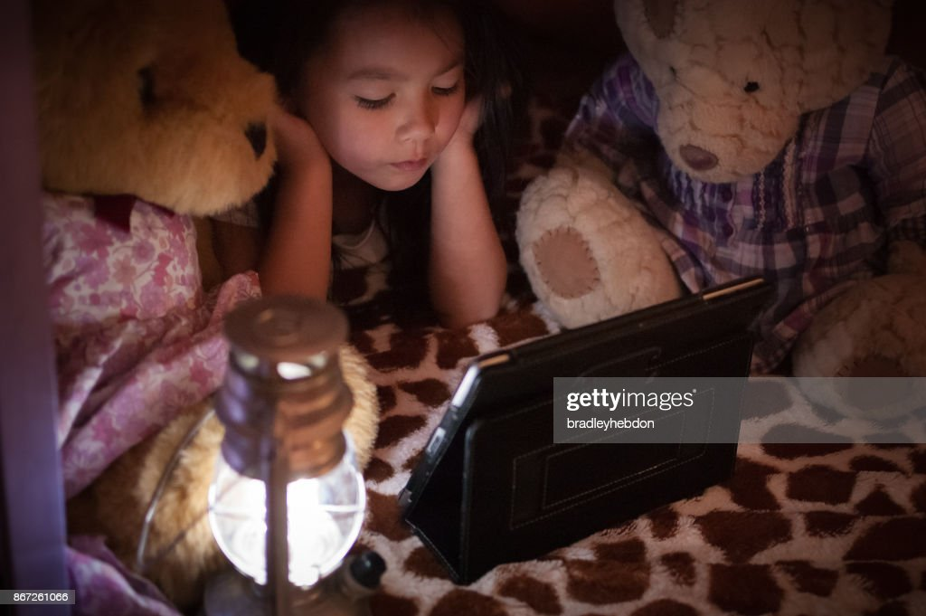 Little girl watching video on tablet with teddy bears : Stock Photo