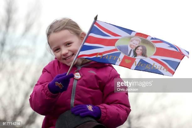 A little girl waves a flag as she awaits the arrival of Prince Harry and Meghan Markle to Edinburgh Castle on February 13 2018 in Edinburgh Scotland