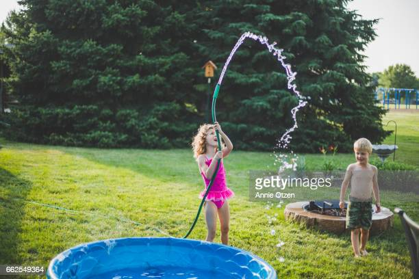 little girl waving a garden hose - annie sprinkle stock pictures, royalty-free photos & images