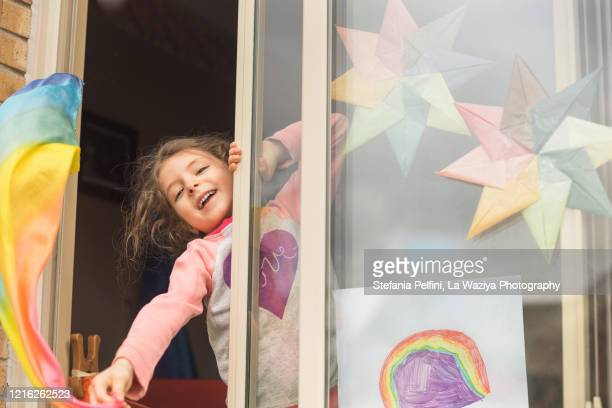 little girl waving her rainbow play silk at her home window during the covid-19 crisis - quedarse en casa frase fotografías e imágenes de stock